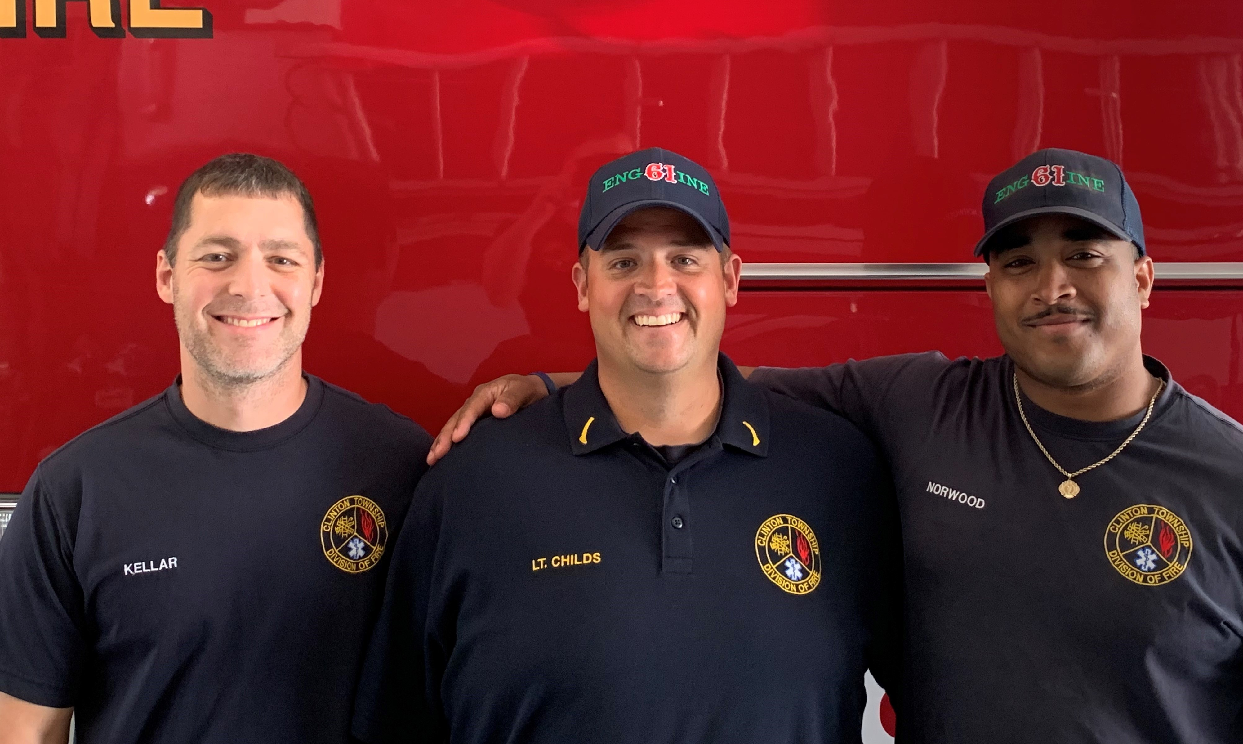 Firefighter Kellar, Fire Lieutenant Childs and Firefighter Norwood are smiling and standing in front of a firetruck.