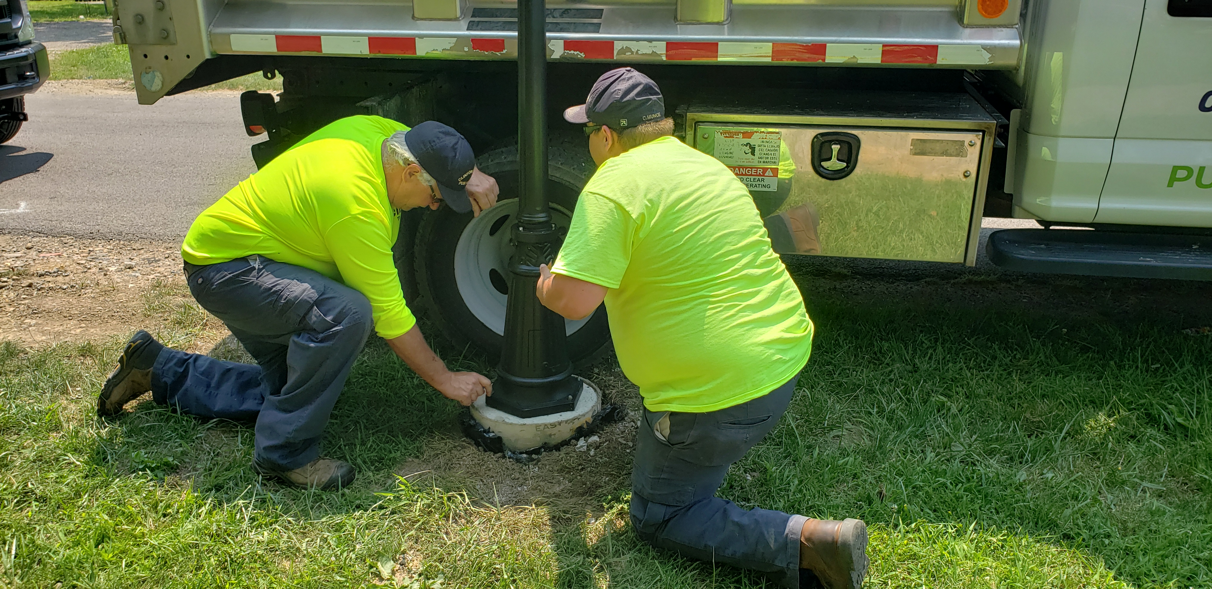 Members of the Clinton Township Public Works crew put the finishing touches on the base of a new solar light.