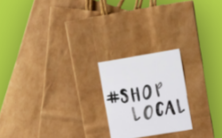 Folded brown shopping bags on a green background. The front bag has a white sticker that reads hashtag shop local.